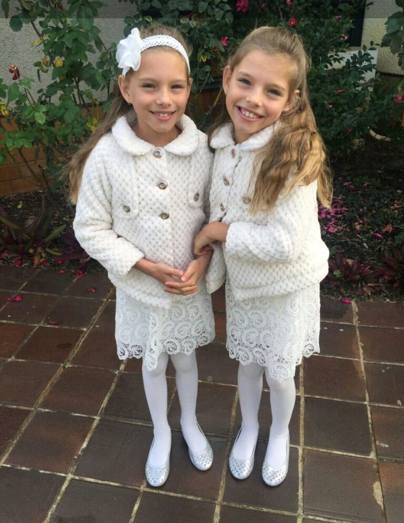 The twins dressed in white smiling for the camera