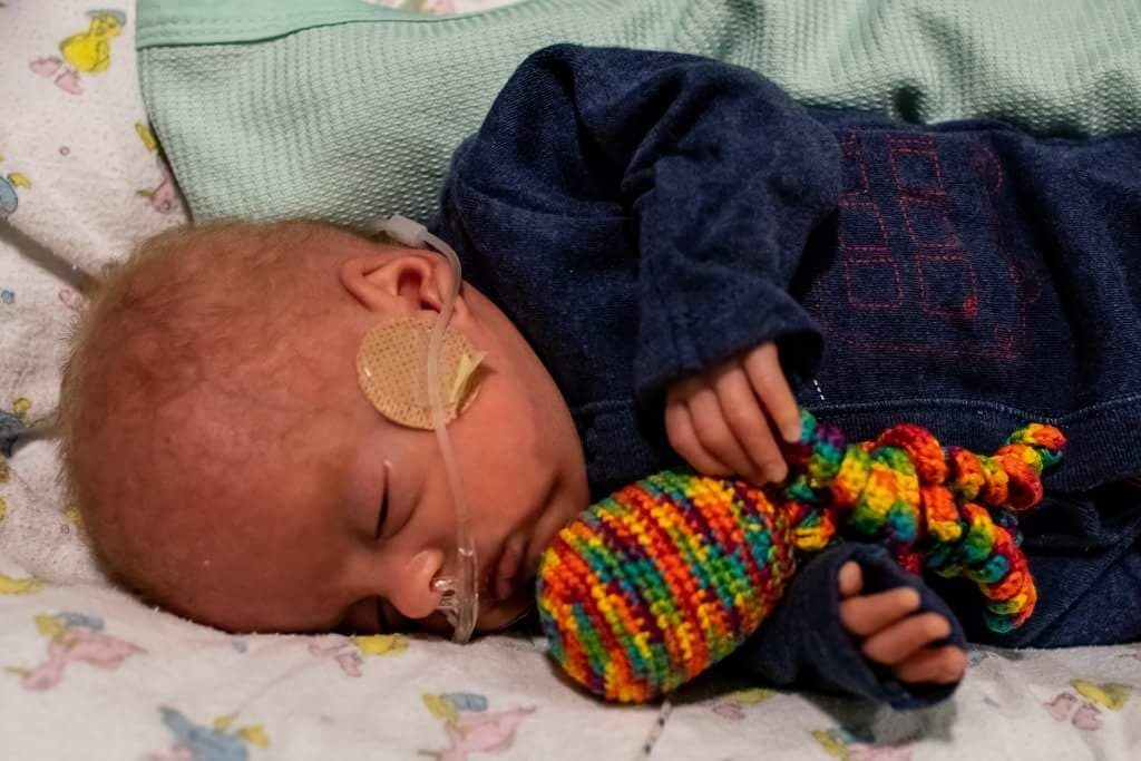 Premature baby holding a rainbow coloured preemie octopus. Photography credit: Izzy Proudfoot
