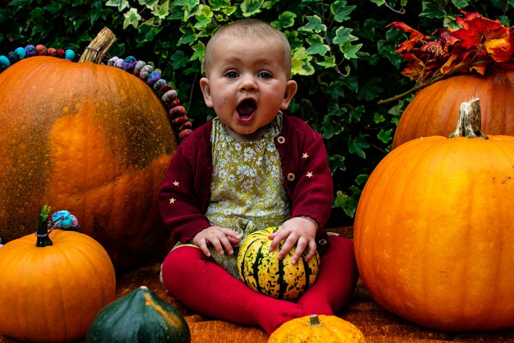 Photograph by Izzy Proudfoot. A happy baby in a pumpkin patch