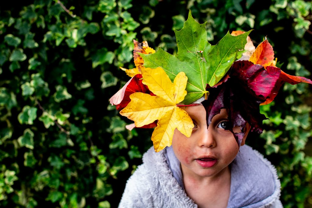 Photo by photographer Izzy Proudfoot of a little boy wearing a crown made of leaves