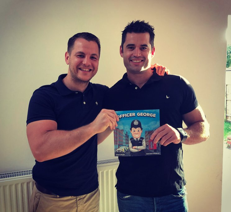Adam Smart and Matthew Boobyer holding the Officer George book they wrote and illustrated