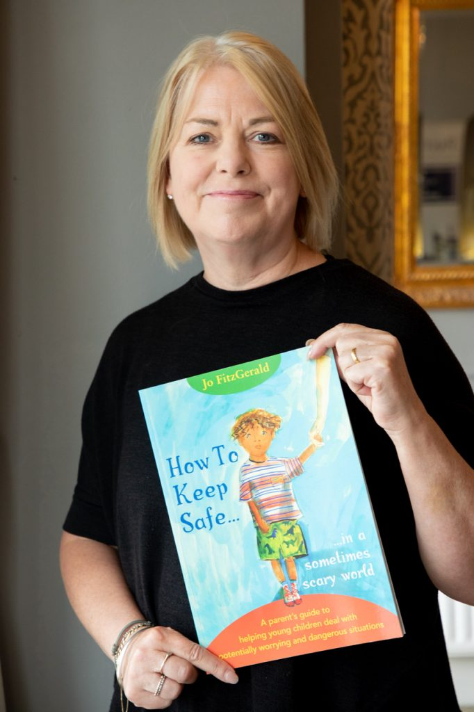 Children's author Jo Fitgerald holding her book How To Keep Safe