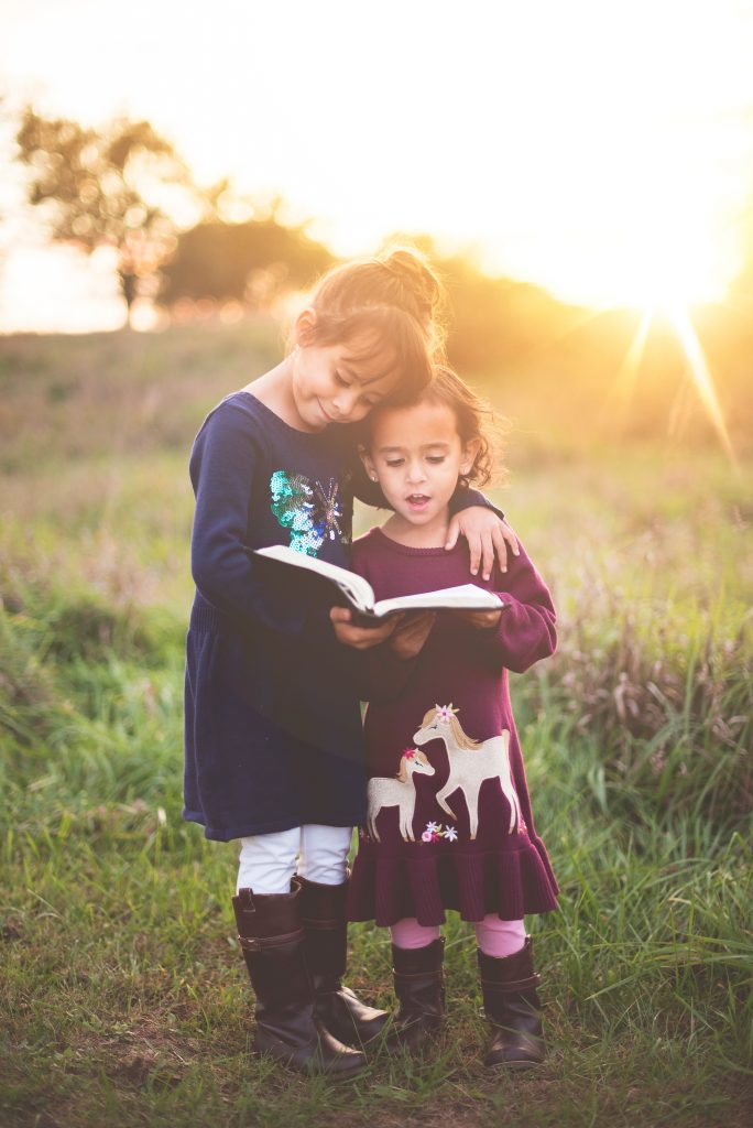 Siblings reading a book together. Photography credit: Ben White