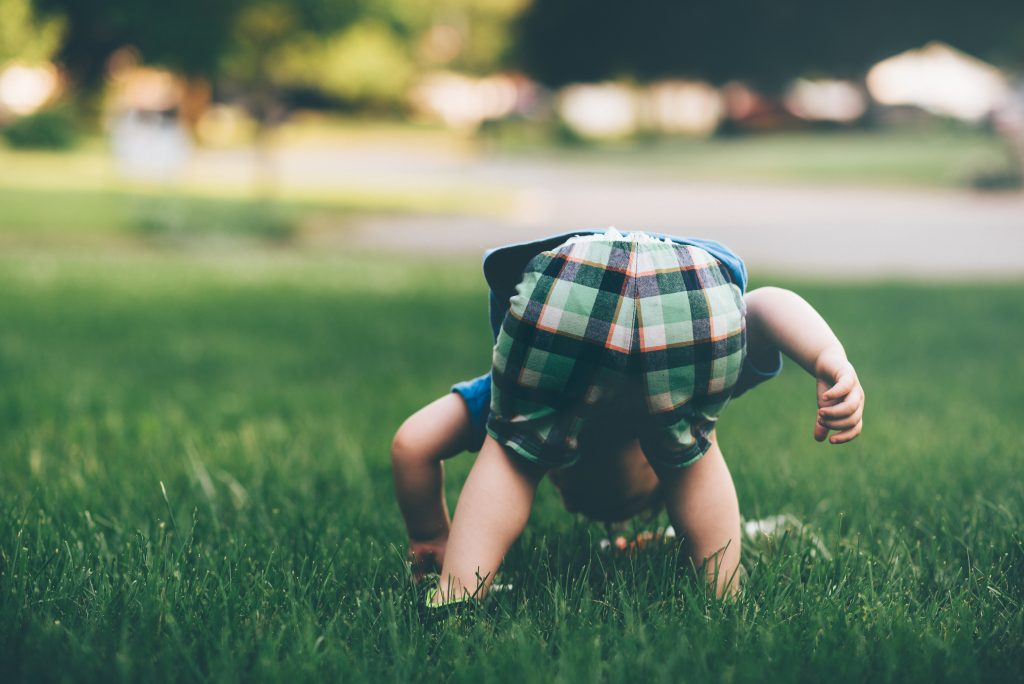 Toddler playing in the grass. Photography credit: Jordan Whitt