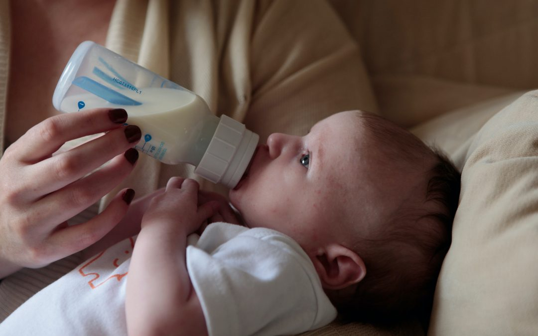 Baby drinking milk from a bottle. Photography credit: Lucy Wolski