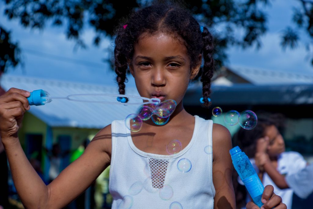 Young girl blowing bubbles. Photography credit: Trust Tru Katsande