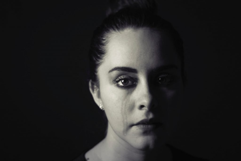Black and white image of a woman crying. Photography credit: Cristian Newman