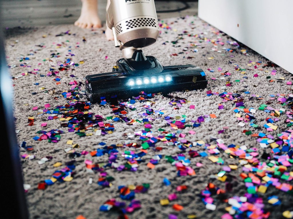 Person vacuuming glitter up from a carpet. Photography credit The Creative Exchange