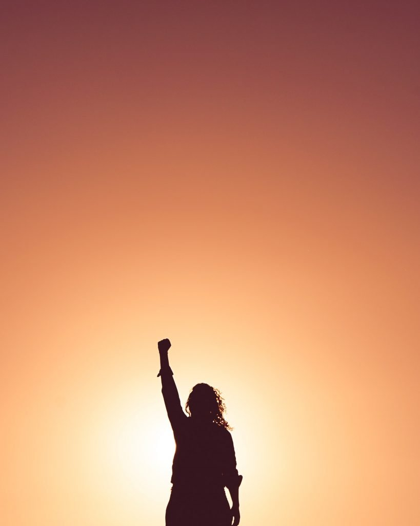 Woman standing confidently with sunset background. Photography credit: Miguel Bruna