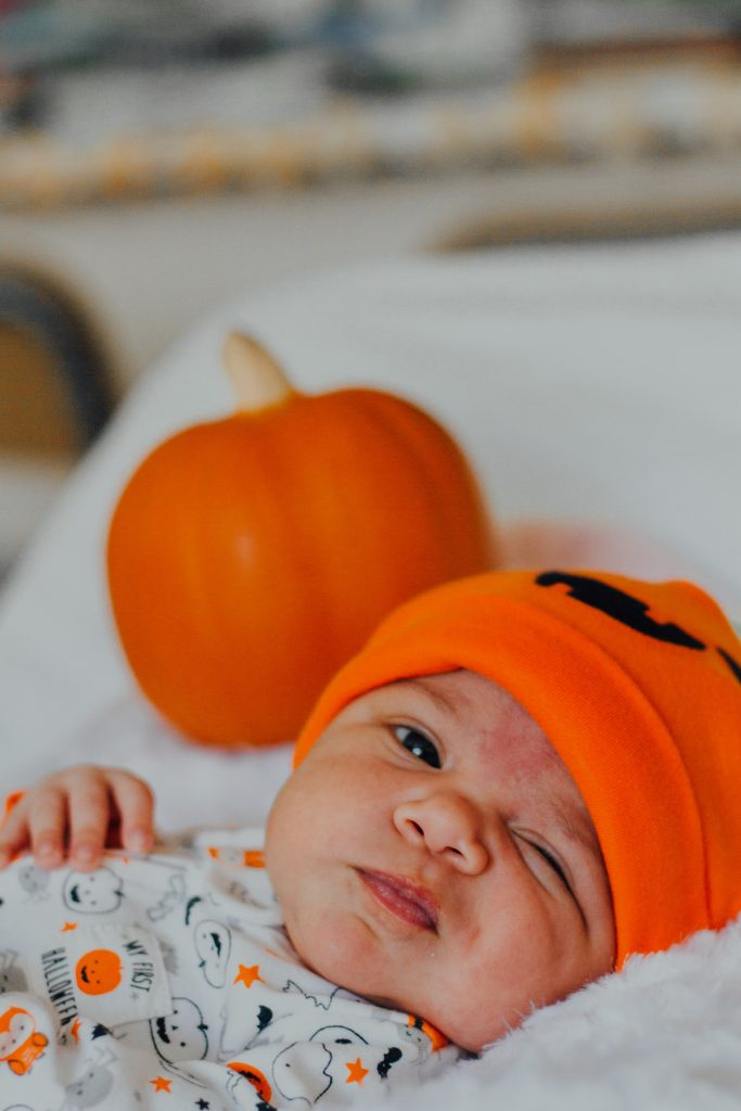 Baby in a pumpkin hat. Photography credit: Omar Lopez