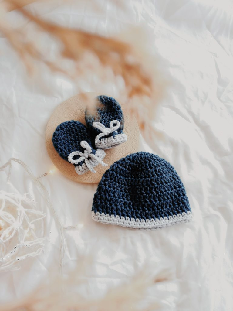 Navy blue and white crocheted baby hat and mittens. Photography credit: Annisa Ica